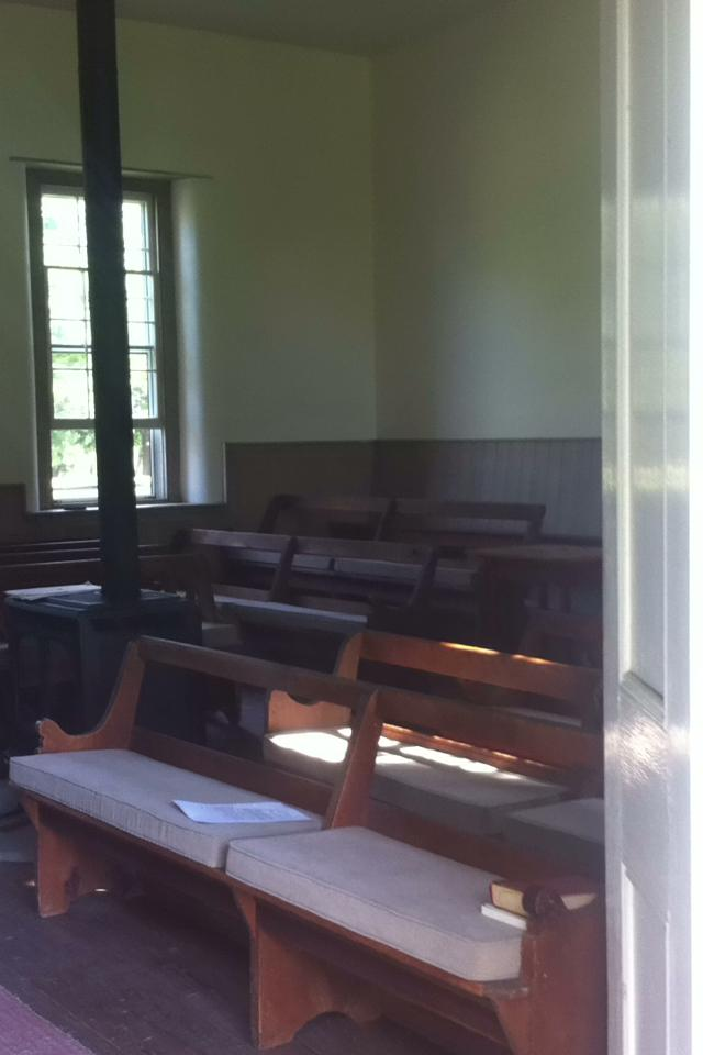 Photo looking into the Meetinghouse, showing Meetinghouse benches (wooden, with cushions) in foreground, wood stove and window in background