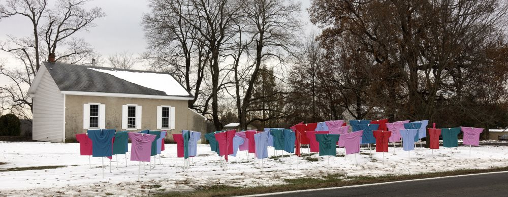Image shows a memorial for victims of gun violence in Bucks County - foreground: t-shirts in different colors are stretched on stakes in the ground and placed in front of the meetinghouse - each t-shirt represents a certain number of gun violence victims. Snow is on the ground. Meetinghouse in background, with trees.