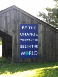 "Photo shows a wooden structure on the meetinghouse grounds. The side of the structure in the photo has a large blue sign that says, in white writing, ""Be the change you want to see in the world."" A picture of the Earth is the ""O"" in ""world."" Grass and trees appear in the foreground and background."