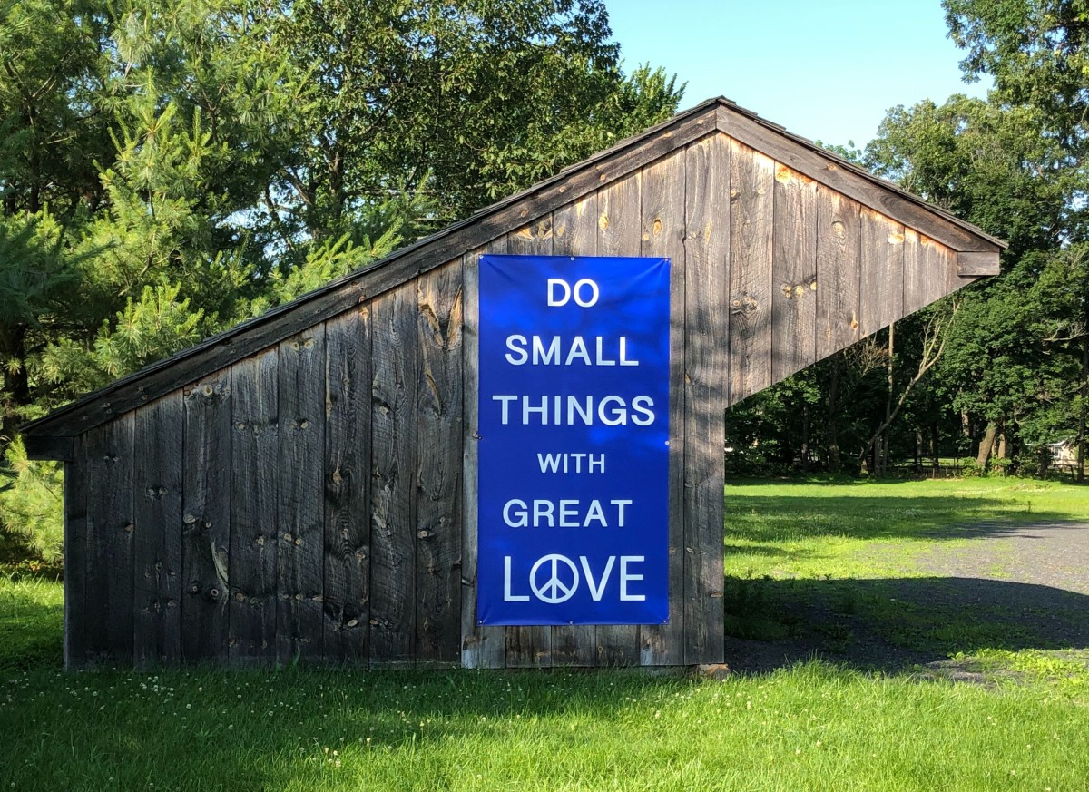 """Photo shows wooden structure on meetinghouse grounds. One side of the structure features a large blue sign that says, in white writing, """"Do small things with great love."""" A peace sign is the """"O"""" in """"love."""" Grass and trees appear in the foreground and background."""